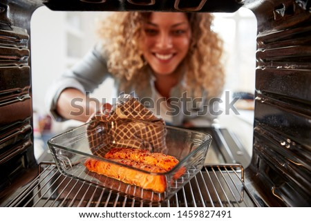 View Looking Out From Inside Oven As Woman Cooks Oven Baked Salmon