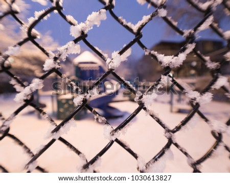 View looking through a snow covered chain link fence to a playground slide on a cold quiet evening in winter in Chicago with blue sky beyond. #1030613827