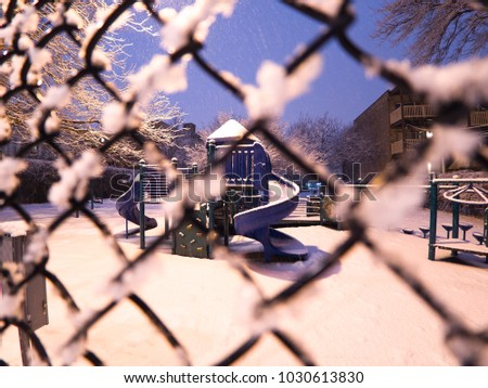 View looking through a snow covered chain link fence to a playground slide on a cold quiet evening in winter in Chicago with blue sky beyond. #1030613830