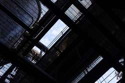 View looking up and out from a dark industrial space through grids and furnaces to blue sky beyond, horizontal aspect
