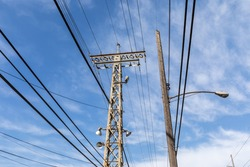 View looking up of metal and wood power structures with electrical cables, street and spot lights against a blue sky with clouds, horizontal aspect