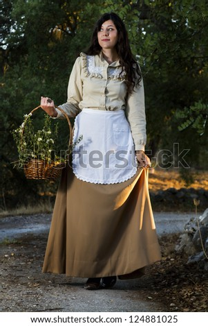 View of a beautiful girl in classic dress wandering on the countryside.