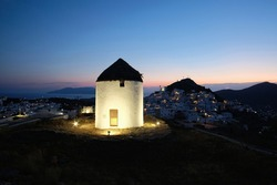 View of a beautiful illuminated white windmill,  while the sun is setting dramatically behind the village of Ios in Greece