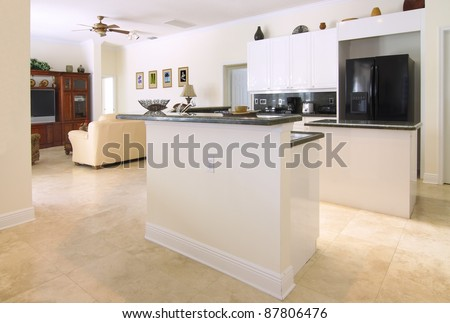 View of a beautiful modern kitchen with upscale appliances, white cabinets, and green granite countertops