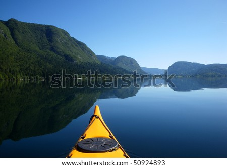 View of a beautiful mountain lake with sea kayak in the foreground