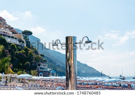 View of a beautiful, new, beach shower on the beach. Mountains in the background. Glossy stainless steel products. Chrome and Nekel resistant coating from the environment. Positano Italy Stock fotó ©