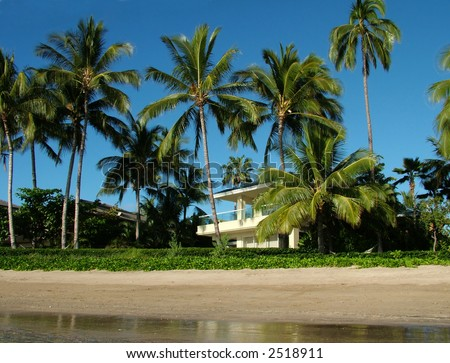 View of a beautiful private home in a tropical setting right on the beach