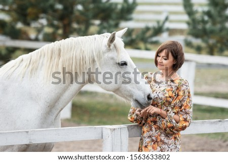 View of a beautiful women in  dress with a white horse on the countryside.photo with animals.equitation.