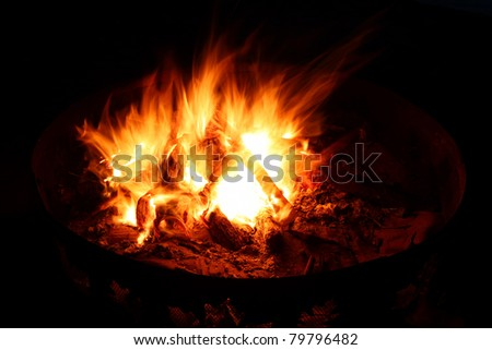 View of a blazing campfire in the dark night - stock photo