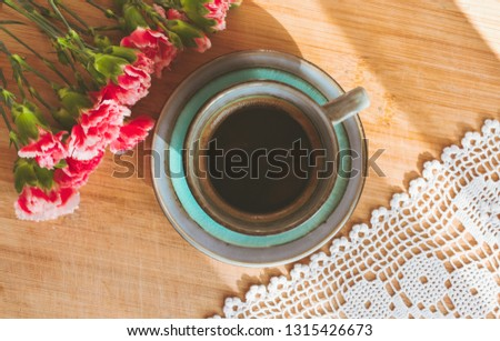 View of a blue porcelain vintage cup of coffee, bouquet of pink carnation flowers and a white doily on wooden background illuminated by sun rays creating shadows on wooden table. Good morning concept #1315426673