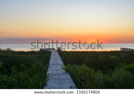View of a boardwalk out to the sound during sunset on the Outer Banks of North Carolina. #1506174806
