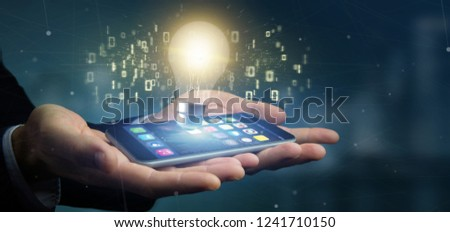 View of a Businessman holding a bulb lamp idea concept with data all around 3d rendering #1241710150