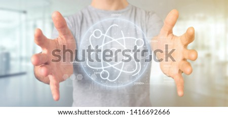 View of a Businessman holding an atom icon surrounded by data #1416692666