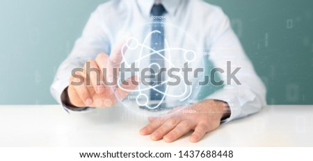 View of a Businessman holding an atom icon surrounded by data #1437688448