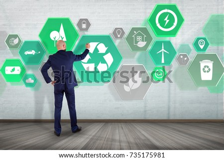 View of a Businessman in front of a wall with Technology ecologic interface  #735175981