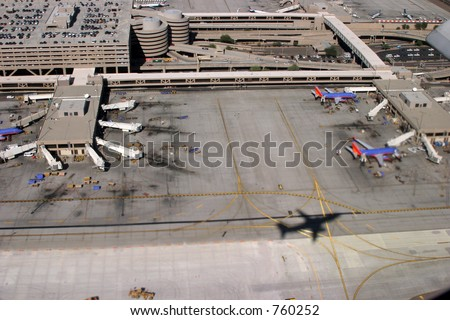 View of a busy airport from the sky with airplane shadow on the ground