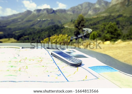 View of a cell phone on top of a map on the roof of a car, South Africa