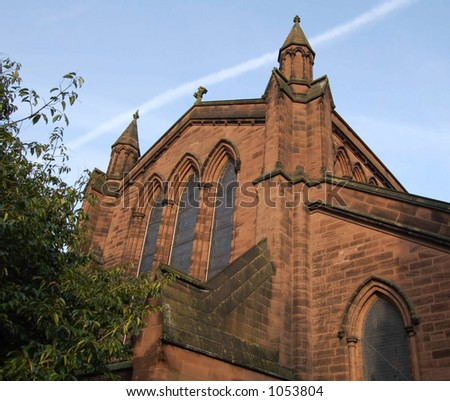 View of a church from one end showing the side and windows with a blue sky.This church is located in the Roman city of Chester,UK