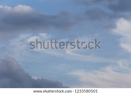 View of a cloudy sky during a sunny afternoon in France, during the autumn season. White and grey lighted clouds with a blue natural background. Abstract picture of space, #1233580501