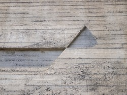 View of a concrete wall with horizontal and diagonal lines on which light falls.