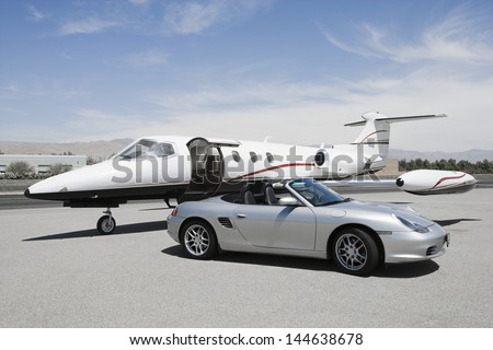 View of a convertible and private jet on landing strip in airport