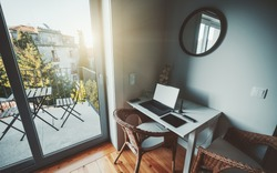 View of a cozy nook in an apartment interior with a desktop of a designer or a digital artist workspace: a laptop, USB hub, cellphone, graphic tablet and pen on the table, balcony on the left