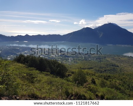 View of a crater lake, the village and the fields with mountains in the background  #1121817662