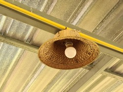 View of a creative bamboo farmer hat light lamp hanging in the roof of local restaurant