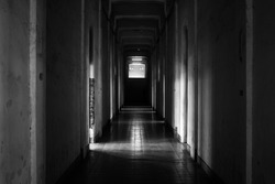 View of a dark corridor in an abandoned old building. Horror, haunted and scary. Black and white image. No people. Used for background or wallpaper.