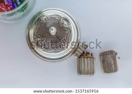 View of a decorative antique metallic objects, vintage - retro metal cup and metal matchbox, isolated, white background with shadow #1537165916