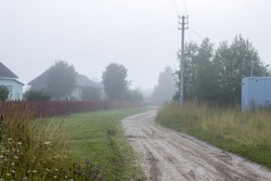 View of a deserted village street. Morning fog. Summer rural foggy landscape. Dirt road, fences and wooden houses. Everyday life in the countryside.
