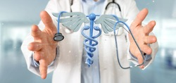 View of a Doctor holding a 3d redering medical cadaceus and stethoscope
