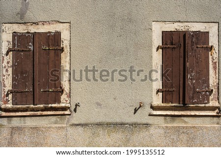 View of a dreary house facade with two closed ailing shutters  Photo stock ©