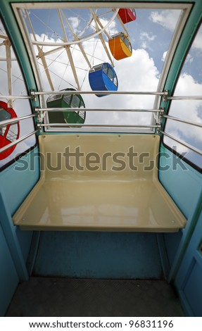 View of a ferris wheel from inside a carousel cab high above ground. - stock photo