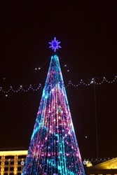 View of a festive tree in winter with multi-colored illumination. The central square of Minsk in the new year.