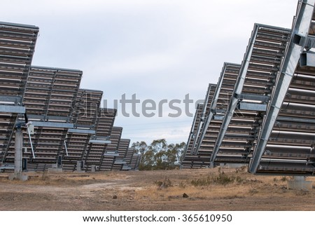 View of a field of photovoltaic solar panels gathering energy on the countryside. #365610950