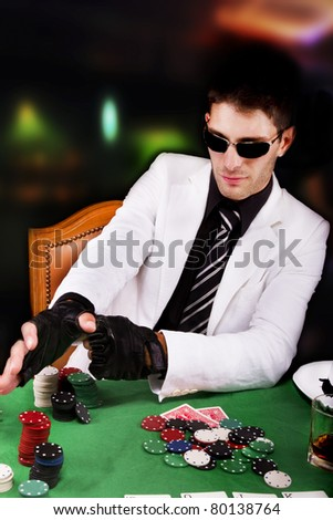 View of a gangster man playing some cards and poker.