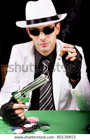 View of a gangster man playing some cards and poker, smoking a Cuban cigar.