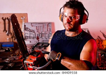 View of a garage mechanic man holding a chainsaw.