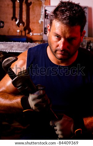 View of a garage mechanic man holding an adjustable spanner.
