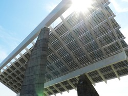 View of a giant solar panel in Parc del Forum, Barcelona, Catalonia/Spain. Sun behind the solar panel with sunbeams.