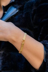 View of a gold bracelet on the wrist of a beautiful woman
