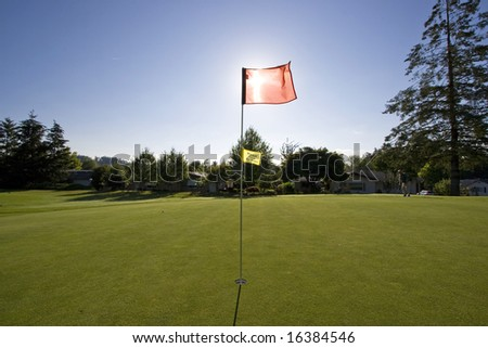 View of a golf course as the sun is going down.  The flag is blocking the sun.  Horizontally framed shot.