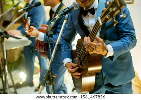 View of a guitarist playing his acoustic guitar with a band during a wedding reception