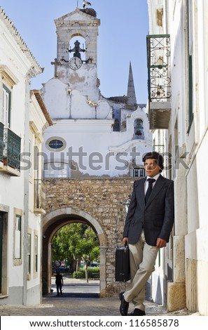 View of a happy business man with a black suitcase on a European city.