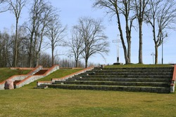 View of a hilltop with some stone stairs and brick pillars leading uphill to the walkway covered with dry withered trees and with a single metal Christian cross in the very middle of the hill