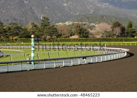 View of a horse racing track with mountains in background. Focus on green and white striped eighth pole.