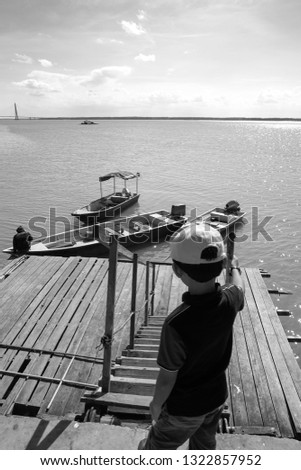 View of a kids watching a man tie a rope to secure his boat to a wooden jetty. view from a wooden jetty #1322857952