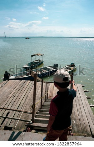 View of a kids watching a man tie a rope to secure his boat to a wooden jetty. view from a wooden jetty #1322857964