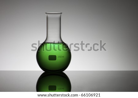view of a laboratory flask with green liquid inside - stock photo
